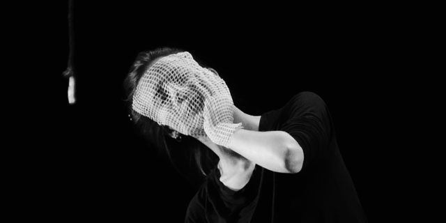 Black and white image. Dancer with face and hand covered by a net mask and glove