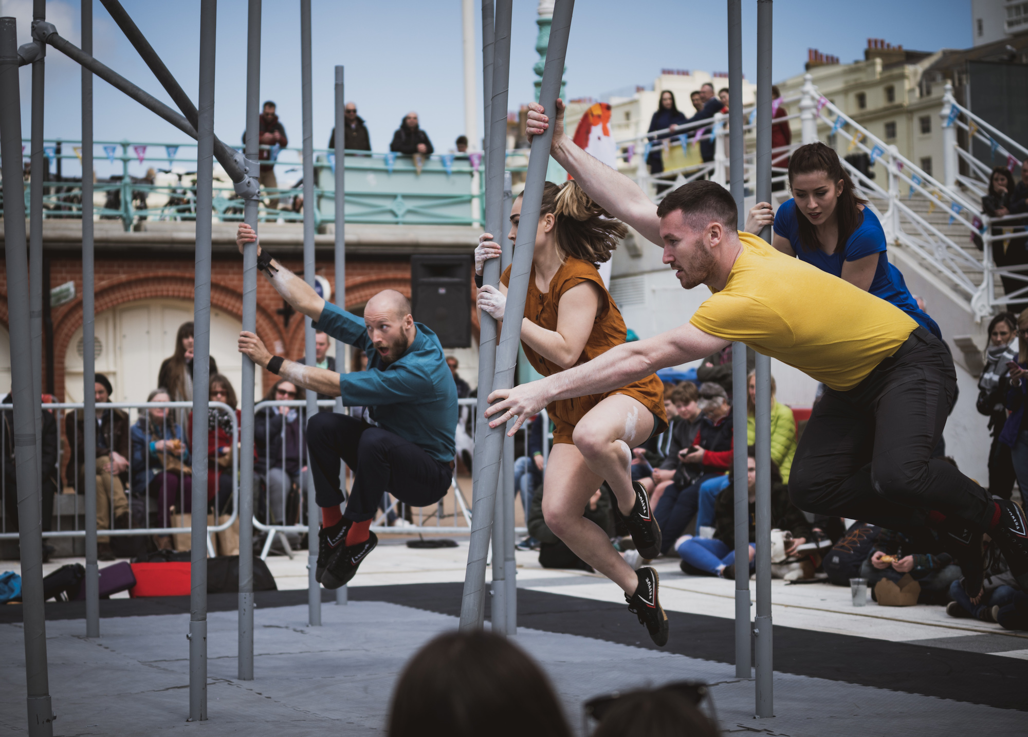 Four acrobatic performers from Motionhouse swing around scaffolding in an outdoor show